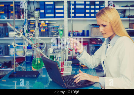 MODEL RELEASED. Female chemist working on a laptop in the laboratory. - Stock Photo