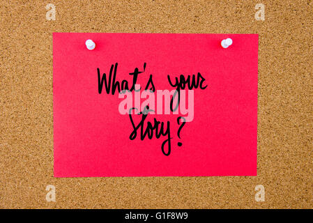 Red paper note with handwritten text What Is Your Story pinned on cork board with white thumbtacks - Stock Photo