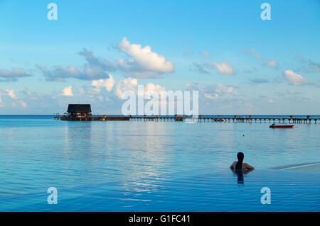 Woman at infinity pool at Olhuveli Beach and Spa Resort, South Male Atoll, Kaafu Atoll, Maldives - Stock Photo
