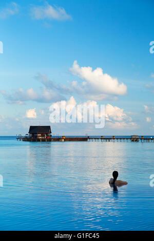 Woman in infinity pool at Olhuveli Beach and Spa Resort, South Male Atoll, Kaafu Atoll, Maldives - Stock Photo
