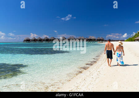 Couple on beach at Olhuveli Beach and Spa Resort, South Male Atoll, Kaafu Atoll, Maldives - Stock Photo