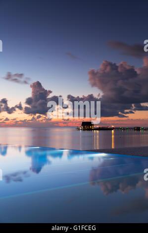 Infinity pool at Olhuveli Beach and Spa Resort at sunset, South Male Atoll, Kaafu Atoll, Maldives - Stock Photo