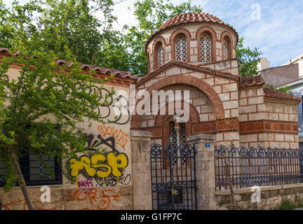 Athens, Greece - April 30, 2016: Church Agia Paraskevi Agioi Anargyroi and graffitti in Psirri neighborhood in Athens. - Stock Photo
