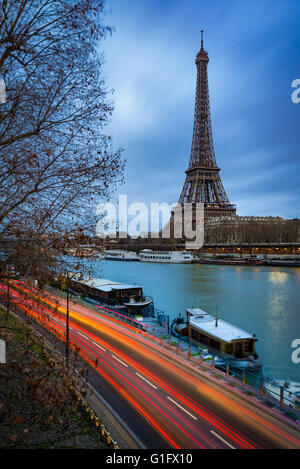 Eiffel Tower at twilight on a cloudy winter morning with the Seine River and car light trails. Paris, 7th Arrondissement, - Stock Photo
