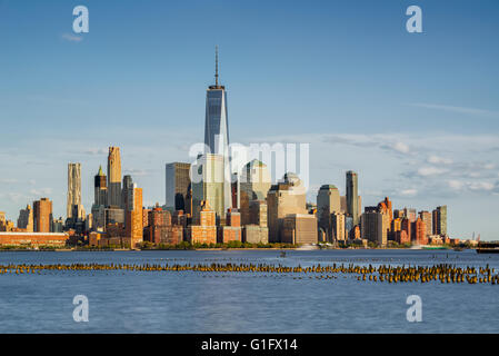 New York City Manhattan Financial District skyscrapers and Hudson River with wooden pilings at sunset