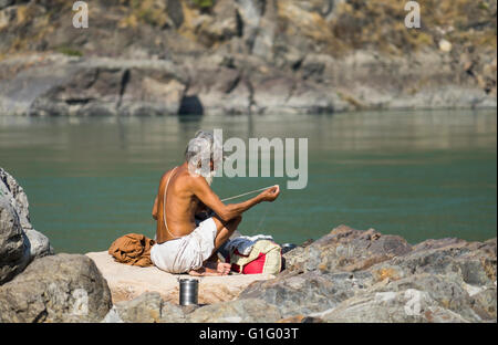 Holy man tending his clothing on the bank of the Ganges, Rishikesh, INdia. - Stock Photo