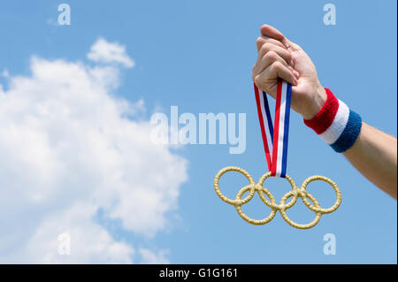 RIO DE JANEIRO - FEBRUARY 4, 2016: Hand with red white and blue wristband holding gold Olympic rings medal hanging - Stock Photo