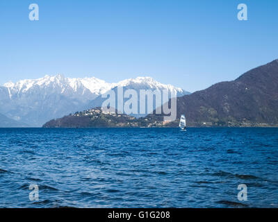 Pianello del Lario, Como - Italy: Windsurfer sailing on the lake and in the background you can see the peninsula - Stock Photo
