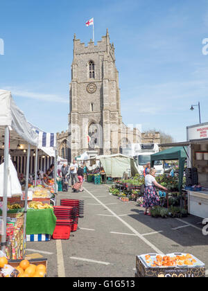 Sudbury's Market Hill on a Saturday, showing the local weekly market and St Peter's church in the background. - Stock Photo