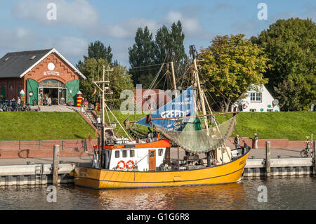 Cafe and fishing boat in harbour of the town of Greetsiel, Lower Saxony, Germany - Stock Photo