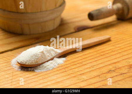 Table spoon with flour on wooden bakery table - Stock Photo