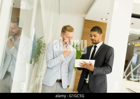 Modern young men with tablet in the modern office - Stock Photo