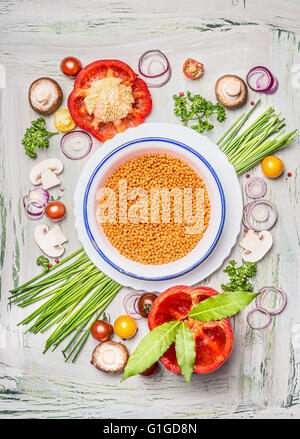 Red lentil in bowl and vegetables ingredients for healthy vegetarian cooking, top view composing. - Stock Photo