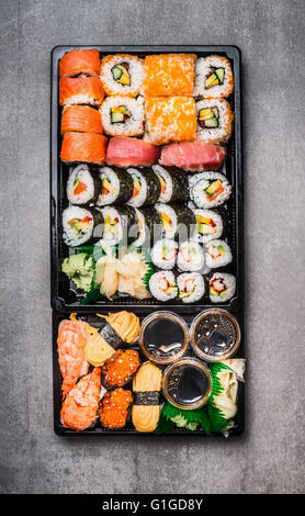 Various Sushi selection in black packaging tray on gray stone background, top view. Top view composing.  Japanese - Stock Photo