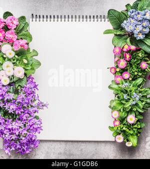 Notebook with garden flowers in pots on stone background, top view. Gardening frame - Stock Photo