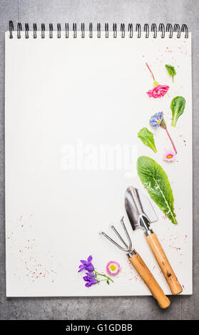 Garden tolls with flowers and petal on blank notebook. Gardening background. - Stock Photo