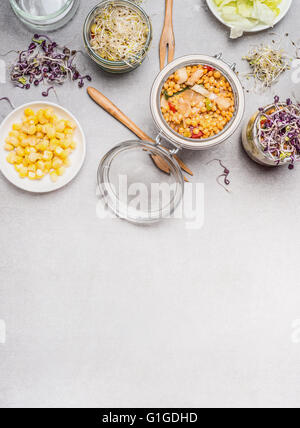 Glass jar salad and vegetables ingredients on light stone background, top view, place for text.  Clean eating, vegetarian - Stock Photo