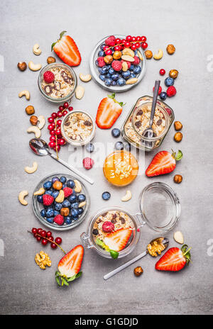 Muesli or granola in jars, fresh berries, seeds and  nuts  , top view. Healthy breakfast flat lay - Stock Photo