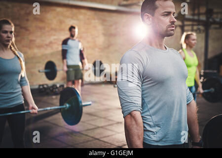 Fit young man lifting barbells looking focused, working out in a gym with other people - Stock Photo