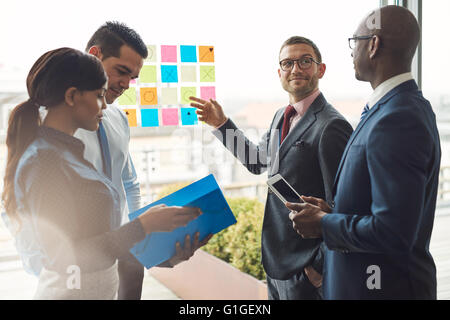 Young group of diverse business people in conference meeting using colorful sticky notes to organize ideas on large - Stock Photo