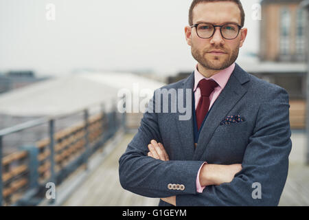 Stylish serious handsome bearded young businessman in eyeglasses, red necktie and folded arms outside on balcony - Stock Photo