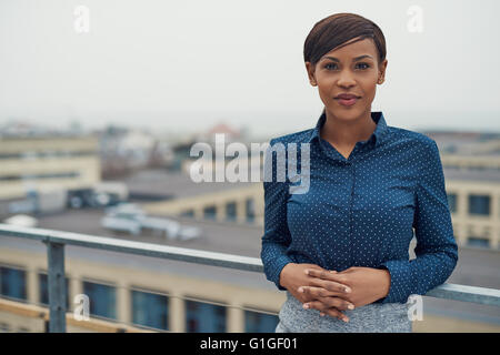 Single calm business woman with folded hands leaning against railing outside with overcast urban skyline and copy - Stock Photo