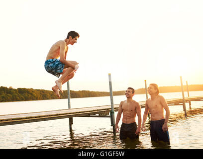 Teenage boy jumping into a lake from a old pier bridge watched by two of his friends as they relax on summer camp, - Stock Photo