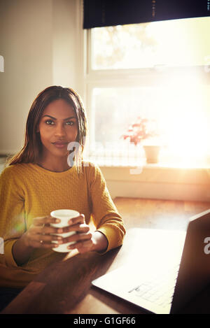 Calm single woman in yellow sweater sitting at table holding coffee cup next to open laptop with bright sun coming - Stock Photo