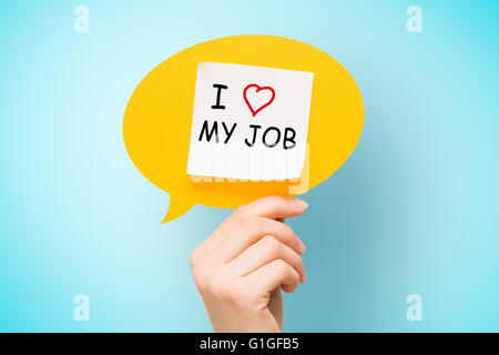 Adhesive note on yellow speech bubble with 'I love my job' words on blue background. - Stock Photo