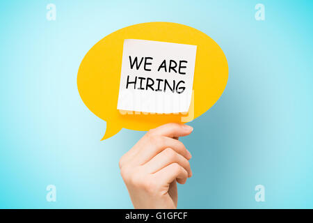 Adhesive note on yellow speech bubble with 'we are hiring' words on blue background. - Stock Photo