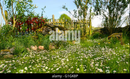 Idyllic garden with blooming flowers in white, blue, yellow and red. - Stock Photo