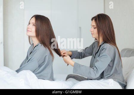 Concentrated pretty young woman in grey pajamas sitting on bed and brushing her sistes twin hair - Stock Photo