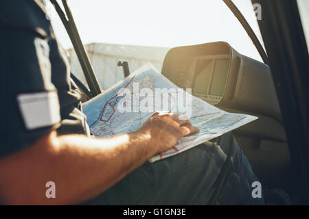 Close up shot of a helicopter pilot studying the flight route map while sitting in the cockpit of the aircraft. - Stock Photo