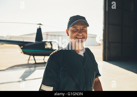Portrait of happy male pilot standing in airplane hangar with a helicopter in background - Stock Photo