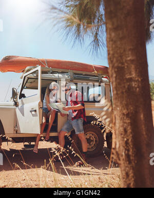 Young couple stopping on country road and looking for directions on the map. Man and woman on a road trip. - Stock Photo