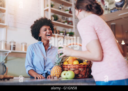 Portrait of young african woman standing behind juice bar counter and talking with female customer holding a glass - Stock Photo