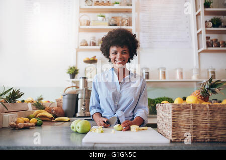 Portrait of beautiful young african woman standing behind the bar counter and chopping fresh fruits. Woman working - Stock Photo