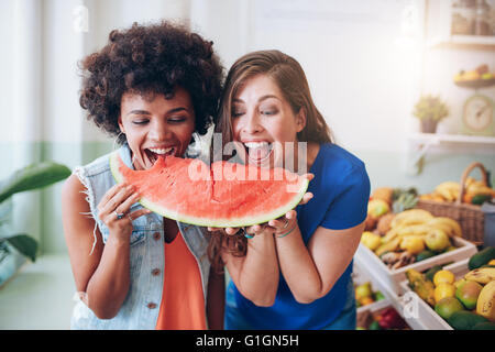 Portrait of cheerful young women taking a bite of a watermelon. Female friends standing together at a juice bar - Stock Photo