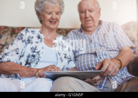 Portrait of happy senior couple sitting together at home and using digital tablet. Elderly man and woman sitting - Stock Photo