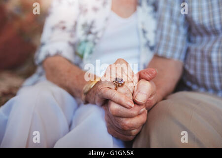 Cropped shot of elderly couple holding hands while sitting together at home. Focus on hands. - Stock Photo