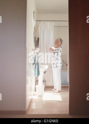 Full length indoor shot of elderly woman getting ready at dresser. Senior female getting ready in bathroom.