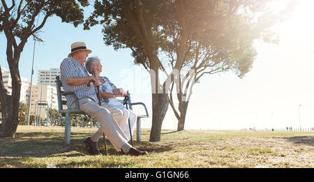Full length outdoor shot of senior couple sitting on a bench on a summer day. Retired man and woman relaxing outdoors. - Stock Photo