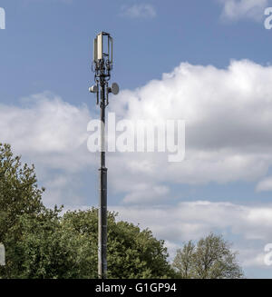 Mobile Telephone Communications Tower against blue sky and trees - Stock Photo