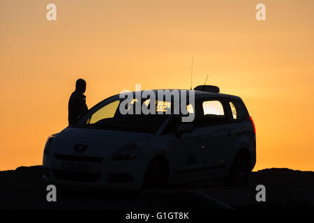 Clarach, Ceredigion, Wales, UK 14th May 2016. UK Weather: Taxi driver parks to watch a Gorgeous sunset on the west - Stock Photo