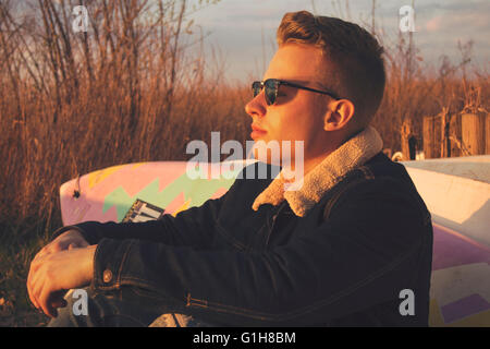 A model watching the sunset, sitting against a surfboard - Stock Photo