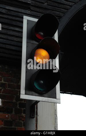 Traffic light showing Yellow for drivers to get ready to stop or drive, Sandwich - Kent - Stock Photo