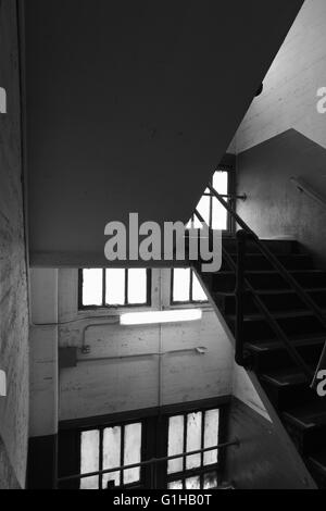 Stairwell in an old concrete industrial building with windows, stairs, and railings, shadows, and perspective - Stock Photo
