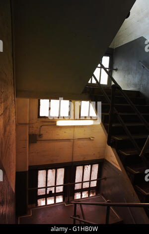 Stairwell in an old concrete industrial building with windows, stairs, and railings, shadows, and perspective. - Stock Photo