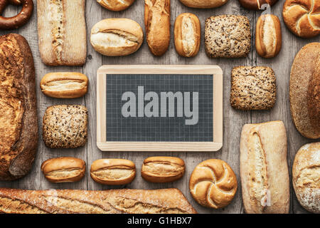 Fresh crisp bread on a wooden worktop and blank chalkboard, bakery and healthy eating concept, flat lay banner - Stock Photo