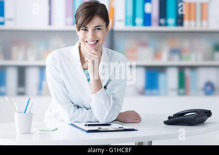Attractive young female doctor leaning on the clinic reception desk with hand on chin, she is smiling at camera, - Stock Photo